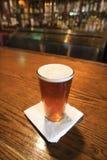 Pinta de cerveza en barra. Foto de archivo