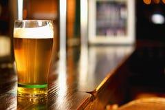 Pinta de cerveza en una barra en un pub del estilo tradicional fotos de archivo