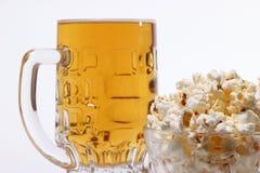 Pinta de cerveza ligera fría y de palomitas saladas Imagenes de archivo