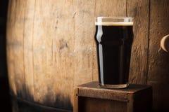 Pinta de cerveza de malta cerca de un barril fotos de archivo libres de regalías