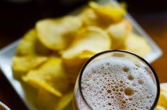 Pinta de la cerveza de cerveza dorada en un vidrio, sistema de diversos bocados, un estándar Imagen de archivo