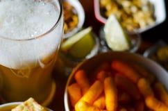 Pinta de la cerveza de cerveza dorada en un vidrio, sistema de diversos bocados, un estándar Foto de archivo libre de regalías