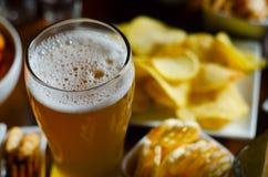 Pinta de la cerveza de cerveza dorada en un vidrio, sistema de diversos bocados, un estándar Fotos de archivo libres de regalías