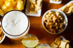 Pinta de la cerveza de cerveza dorada en un vidrio, sistema de diversos bocados, un estándar Imágenes de archivo libres de regalías