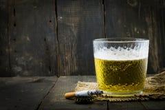 Pinta de la cerveza y de un cigarrillo encendido en el fondo de madera Imagen de archivo