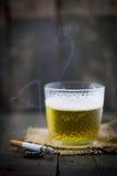 Pinta de la cerveza y de un cigarrillo encendido en el fondo de madera Imagenes de archivo