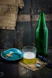 Pinta de la cerveza y de un cigarrillo encendido en el fondo de madera Imagen de archivo libre de regalías