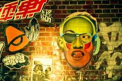Pintada con la cara extraña en la pared de ladrillo Imagen de archivo libre de regalías