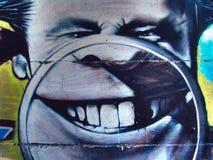 Pintada de la calle en la cabeza pública de la caricatura de la pared de un hombre con la lupa y los dientes Novi Serbia triste 0 Imagen de archivo