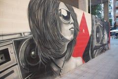 Pintada del arte de la calle de una muchacha que escucha la música ilustración del vector