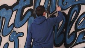 Pintada urbana joven del dibujo del pintor en la pared Fotografía de archivo