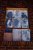 Pintado e Chippy Windows na construção de tijolo imagens de stock