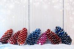 Pintado en diversos conos de abeto de los colores están mintiendo aleatoriamente en nieve en fondo de madera ligero Fotos de archivo