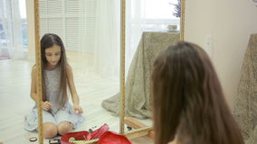 Pintan a la niña antes de un espejo su maquillaje del ` s de la madre almacen de video