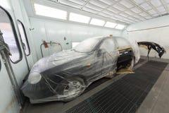 Pintando a porta e o amortecedor de carro na loja de corpo Fotos de Stock Royalty Free