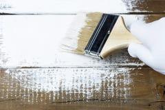 Pintando uma superfície de madeira com pintura branca, uma mão gloved que guarda uma escova de pintura fotografia de stock