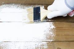 Pintando uma superfície de madeira com pintura branca, uma mão gloved que guarda uma escova de pintura fotos de stock