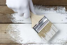 Pintando uma superfície de madeira com pintura branca, uma mão gloved que guarda uma escova de pintura fotografia de stock royalty free