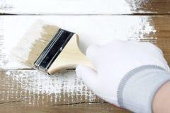 Pintando uma superfície de madeira com pintura branca, uma mão gloved que guarda uma escova de pintura foto de stock royalty free