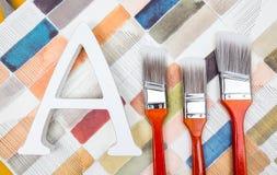 Pinte as escovas e a letra A no fundo da aquarela fotografia de stock royalty free