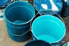 Pinte a cubeta suja com cor azul no asfalto com pincel Pintura velha em umas latas desarrumado, oxidadas prontas para reciclar Fotografia de Stock Royalty Free