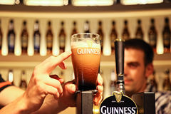 Pinte de Guinness avec l'indication par les doigts Photographie stock libre de droits