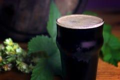 Pinte de mousse de bière foncée admirablement sur un baril avec une feuille de fond d'houblon photographie stock libre de droits