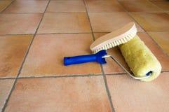 Pinte la lechada de cal, accesorios, herramientas, cepillo, rollo en piso rústico Imágenes de archivo libres de regalías