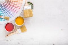 Pinte las latas paleta de colores, latas abiertas con los cepillos en el verraco blanco Foto de archivo libre de regalías