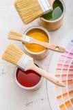 Pinte las latas paleta de colores, latas abiertas con los cepillos en el verraco blanco Fotografía de archivo