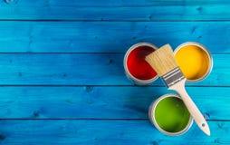 Pinte las latas paleta de colores, latas abiertas con los cepillos en la tabla azul Imágenes de archivo libres de regalías