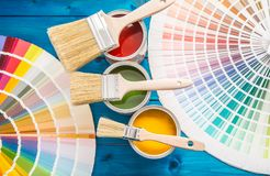 Pinte las latas paleta de colores, latas abiertas con los cepillos en la tabla azul Fotografía de archivo