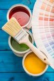 Pinte las latas paleta de colores, latas abiertas con los cepillos en la tabla azul Imagen de archivo