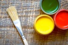 Pinte latas com escova em uma opinião superior do fundo de madeira Imagens de Stock