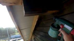 Pinte o reparo de paredes de madeira da casa da rua em um dia de verão vídeos de arquivo