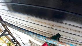 Pinte o reparo de paredes de madeira da casa da rua em um dia de verão video estoque