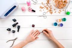 Pinte seus próprios pregos Grupo e verniz para as unhas de tratamento de mãos no fundo de madeira Imagens de Stock