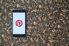 Pinterest-Logo auf Smartphone auf Hintergrund von kleinen Steinen Stockfoto