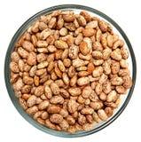 Pinto Beans Raw Unwashed en bol de vidrio sobre blanco Imagen de archivo libre de regalías