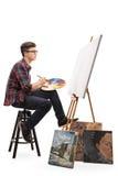 Pintor adolescente con la brocha y la paleta que miran la lona Foto de archivo libre de regalías