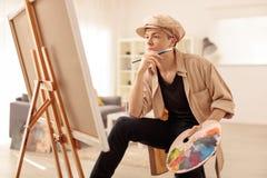 Pintor adolescente pensativo que mira una lona Imagenes de archivo