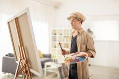 Pintor adolescente que mira una lona en casa Imagenes de archivo