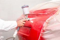 Pintor auto que rocía la pintura roja en el coche en taller auto Imágenes de archivo libres de regalías