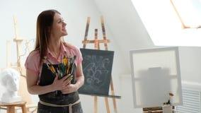 Pintor bonito novo da mulher entre armações e lonas em um estúdio brilhante filme