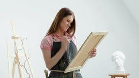 Pintor bonito novo da mulher entre arma??es e lonas em um est?dio brilhante Inspira??o e passatempo video estoque