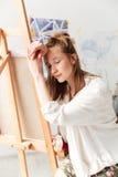 Pintor caucásico joven cansado de la señora en el espacio de trabajo Imágenes de archivo libres de regalías