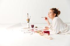 Pintor caucásico joven concentrado de la señora en el espacio de trabajo Imagenes de archivo