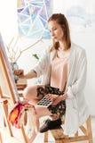 Pintor caucásico joven hermoso de la señora en el espacio de trabajo Fotografía de archivo libre de regalías