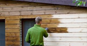 Pintor com a fachada da casa da pintura do pincel com cor protetora de madeira video estoque