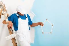 Pintor con el paintroller que muestra una casa del criterio Foto de archivo libre de regalías